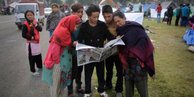 Survivors of Saturday's earthquake read the newspaper at a makeshift camp in Kathmandu, Nepal, Tuesday,...