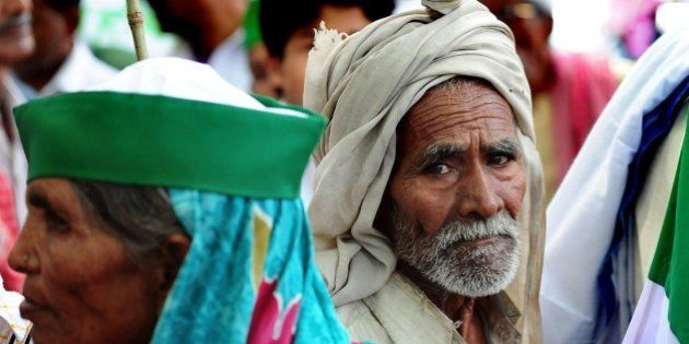 An Indian farmer of the Bharatiya Kisan Union (BKU) - Indian Farmers' Union - listens to a speech by...