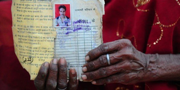 Sita Devi, the mother of Indian farmer Pyare Lal Bind, 45, and who committed suicide after his crops failed, poses for a photograph with an image of her son and the family's ration card Karnipur village, some 35 kms away from Allahabad on April 18, 2015. Unseasonal heavy rains has caused crops to fail across parts of India. AFP PHOTO/ SANJAY KANOJIA        (Photo credit should read Sanjay Kanojia/AFP/Getty Images)