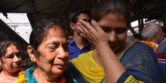 Indian resident Santosh (2L) is met by relatives after being evacuated following an earthquake in Nepal at the railway station in Amritsar on April 27, 2015. International aid groups and governments intensified efforts to get rescuers and supplies into earthquake-hit Nepal on April 26, 2015, but severed communications and landslides in the Himalayan nation posed formidable challenges to the relief effort. As the death toll surpassed 2,000, the US together with several European and Asian nations sent emergency crews to reinforce those scrambling to find survivors in the devastated capital Kathmandu and in rural areas cut off by blocked roads and patchy phone networks. AFP PHOTO/NARINDER NANU        (Photo credit should read NARINDER NANU/AFP/Getty Images)