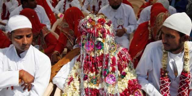 An Indian groom sits decorated with flowers during a mass marriage ceremony in Ahmadabad, India, Saturday,...