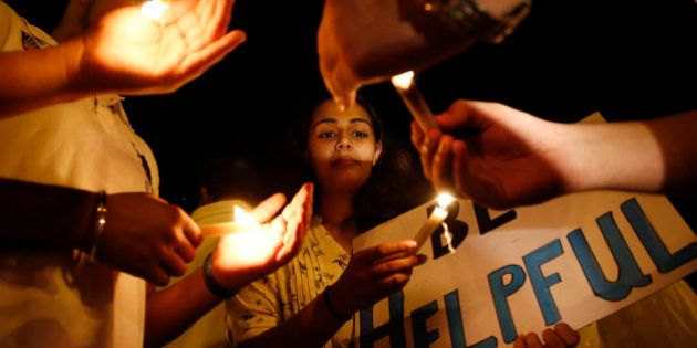 A college student participates in a candle light vigil for victims of Nepal's earthquake, in Mumbai,...