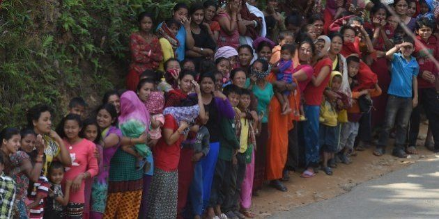 Nepalese people queue for relief aid from an Indian Air Force (IAF) helicopter team in northern-central...