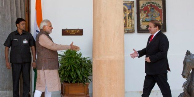 Indian Prime Minister Narendra Modi, left, walks to shake hand with his Pakistani counterpart Nawaz Sharif...
