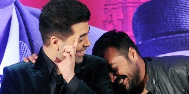 Indian Bollywood actor Karan Johar (L) and writer, director and producer Anurag Kashyap share a light...