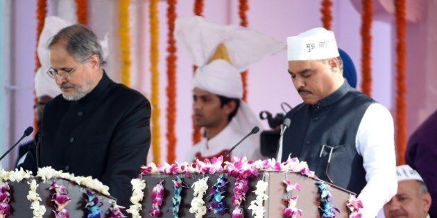 Delhi's Lieutenant Governor Najib Jung (L) adminsters the oath to Aam Aadmi Party (AAP) leader Jitender...
