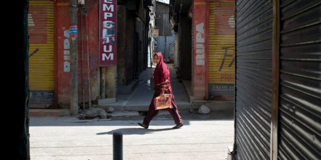 A Kashmiri Muslim woman walks past a closed market are during a strike in Srinagar, Indian controlled...