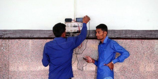 Indian passengers charge their mobile phones at Allahabad Junction in Allahabad on February 26, 2015....