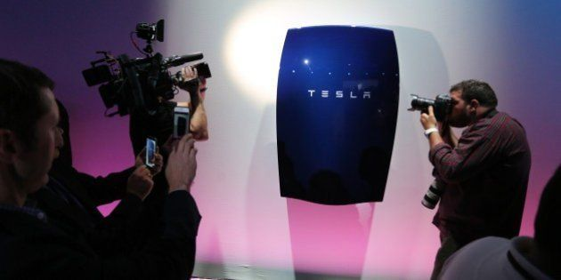 People look at newly-unveiled Tesla Powerwall batteries at the Tesla Design Studio in Hawthorne, California,...