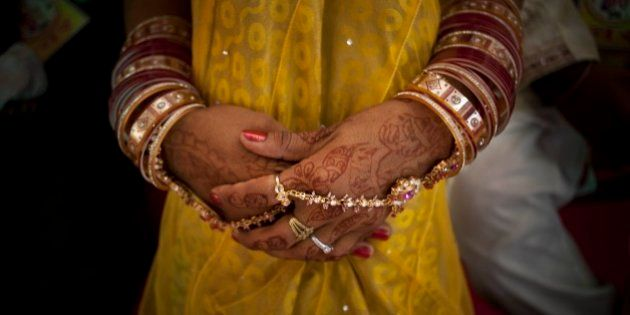 An Indian bride who has her hand decorated waits for a ceremony to begin during a mass wedding organized...