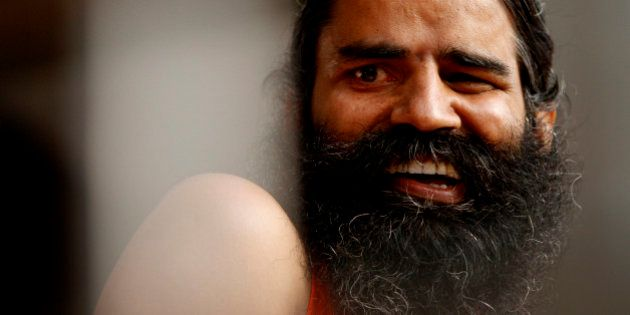 Indian yoga guru Baba Ramdev smiles during an anti-corruption protest in New Delhi, India, Tuesday, Aug....