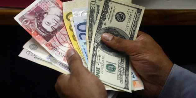 An Indian money changer poses as he counts foreign currency notes in New Delhi on August 27, 2013. The...