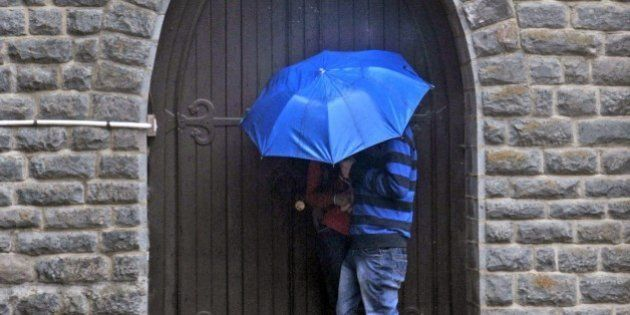 An Indian couple take shelter in a doorway of a church during heavy rainfall in Shimla on February 25,...
