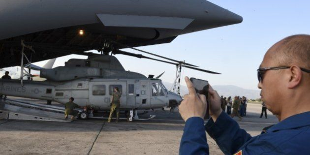 A Chinese air force officer takes a photo with his phone of US military personnel unloading a Huey helicopter...