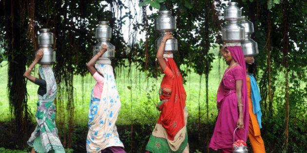 Indian women carry drinking water utensils at Tilakwada village near Sardar Sarovar Narmada Dam on Narmada...
