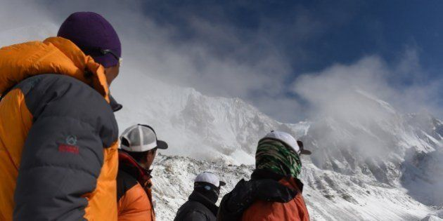 Nepalese Sherpas look up towards an area where an avalanche triggered by an earthquake occurred at Everest...