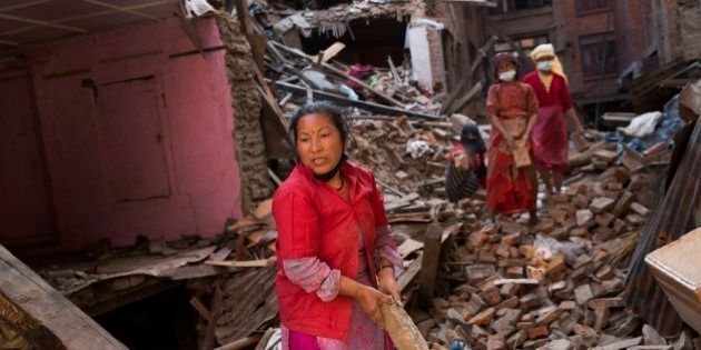 Nepalese women remove debris searching their belongings from their house that was destroyed a week ago...