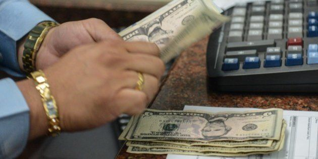 A cashier counts US dollars at a currency exchange office in Caracas on February 19, 2015. The Venezuelan...