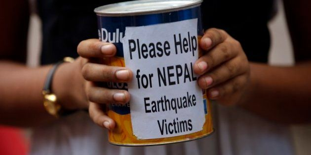 Indian children outside an art school collect relief fund for the victims of Nepal earthquake in Mumbai,...