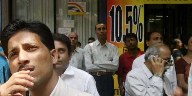 People watch a screen displaying the share prices outside the building of the Bombay Stock Exchange in...