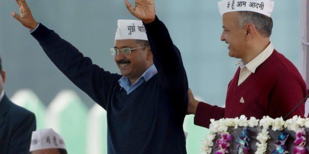Aam Aadmi Party (AAP) president Arvind Kejriwal (L) greets his supporters as fellow Minister Manish Sisodia...