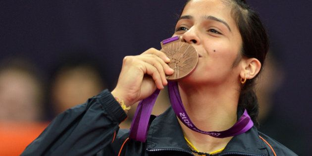 India's Saina Nehwal kisses her bronze medal after beating China's Wang Xin in their bronze medal women's...
