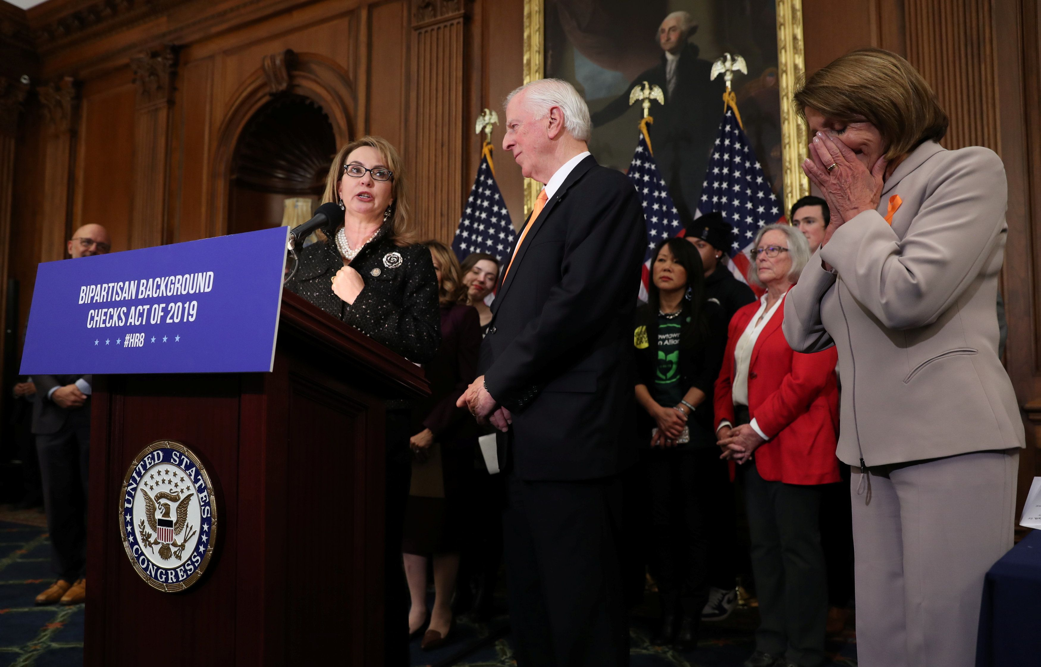 "Former U.S. Rep Gabrielle Giffords, gravely injured in a shooting while serving in Congress, speaks as Rep. Mike Thompson (D-CA) and U.S. House Speaker Nancy Pelosi (D-CA) listen during their news conference announcing the introduction of ""bipartisan legislation to expand background checks for sales and transfers of firearms"" on Capitol Hill in Washington, U.S., January 8, 2019. REUTERS/Jonathan Ernst"