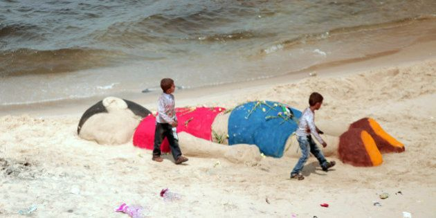In this Monday Sept. 7, 2015 photo, two Palestinian boys play by a sand sculpture paying tribute to three...