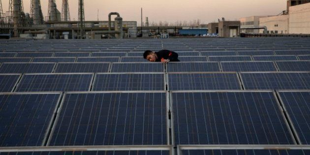 BAODING, CHINA - DECEMBER 4: A technician from Yingli Solar checks a solar panel used to produce energy...