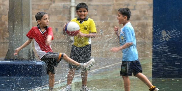 Indian school children play in a puddle after a rain shower in Mumbai on July 18, 2013. The monsoon season,...