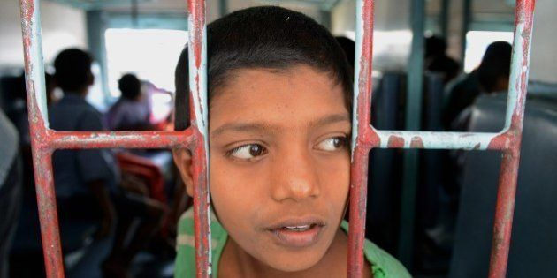 A rescued Indian child labourer looks on on board a Patna-bound express train at a railway station in...
