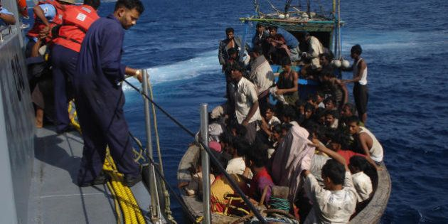 Members of the Indian coastguard rescue illegal Bangladeshi migrants in their trawler after they were...