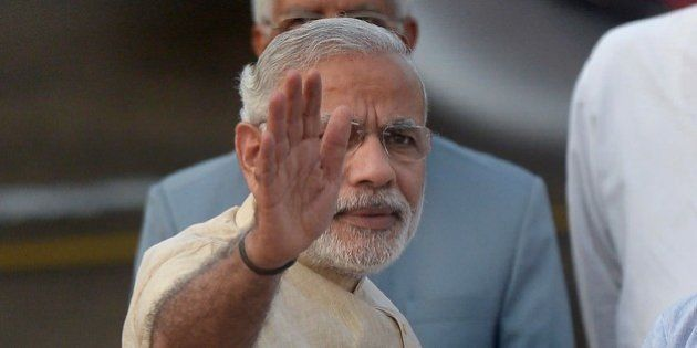 Indian Prime Minister Narendra Modi waves as he exits the aircraft on his arrival at the Netaji Subhas...