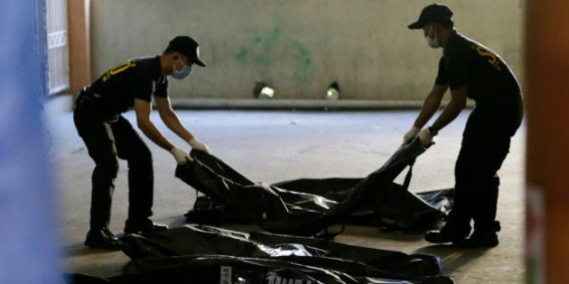Members of Scene of the Crime Operatives of the Philippine National Police line up body bags containing...