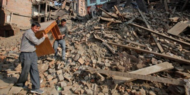 Nepalese people recover their belongings from earthquake destroyed buildings in Bhaktapur, Nepal, Thursday,...
