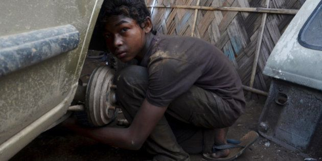Ural Rahul, 15, works on a car at a repair garage in Dimapur, India's northeastern state of Nagaland,...