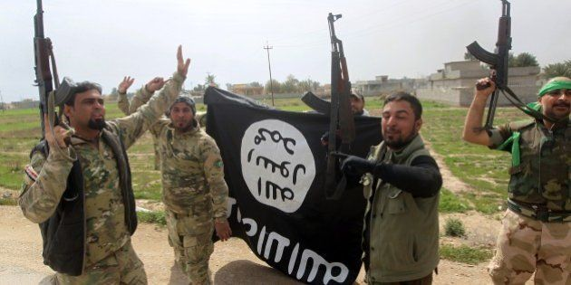Members of the Iraqi paramilitary Popular Mobilisation units celebrate with a flag of the Islamic State...