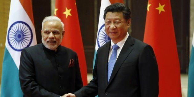 India's Prime Minister Narendra Modi (L) and China's President Xi Jinping shake hands before they hold...