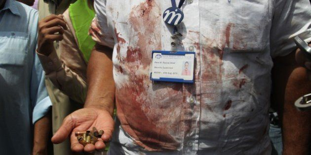 A Pakistani security official displays cartridges he collected from the scene of an attack on a bus,...