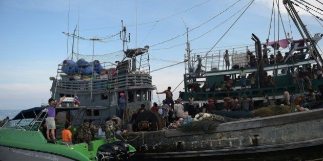Fishermen (C) and National Park officials (L) provide food supplies to Rohingya migrants stranded on...