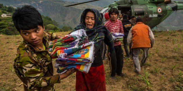 GUMDA, NEPAL - MAY 06: Nepalese villagers collect aid dropped by an Indian helicopter on May 6, 2015...