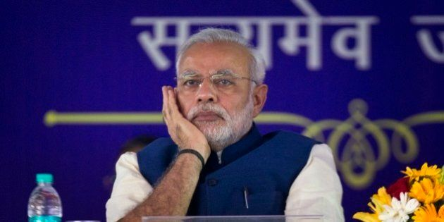Indian Prime Minister Narendra Modi listens to a speaker after unveiling the foundation stone for an...