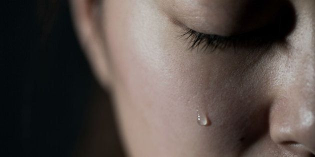 Young woman crying with tear