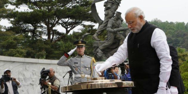 Indian Prime Minister Narendra Modi, right, burns incense at the National Cemetery in Seoul, South Korea,...