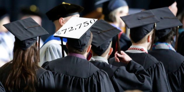 A student in line for his diploma wears a cap decorated with the cost of his education during graduation...