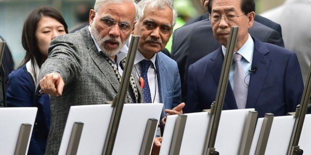 Indian Prime Minister Narendra Modi (L) talks with Seoul Mayor Park Won-Soon (R) as he visits the Cheonggye...