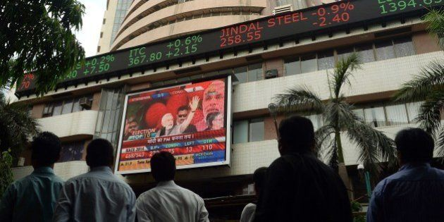 An Indian pedestrian watches as a digital broadcast presents the rolling share price information and...