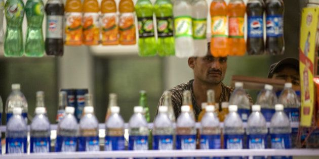 Indian vendor sells cold drinks on the roadside in New Delhi on May 18, 2010, as temperatures in the...