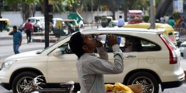 An Indian labourer takes a break as he drinks water to get respite from heat in New Delhi on May 26,...