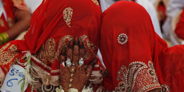 An Indian bride whispers to another during a mass marriage ceremony in Ahmadabad, India, Saturday, March...
